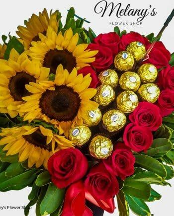 Arreglo floral en forma de corazon con rosas girasoles y chocolates